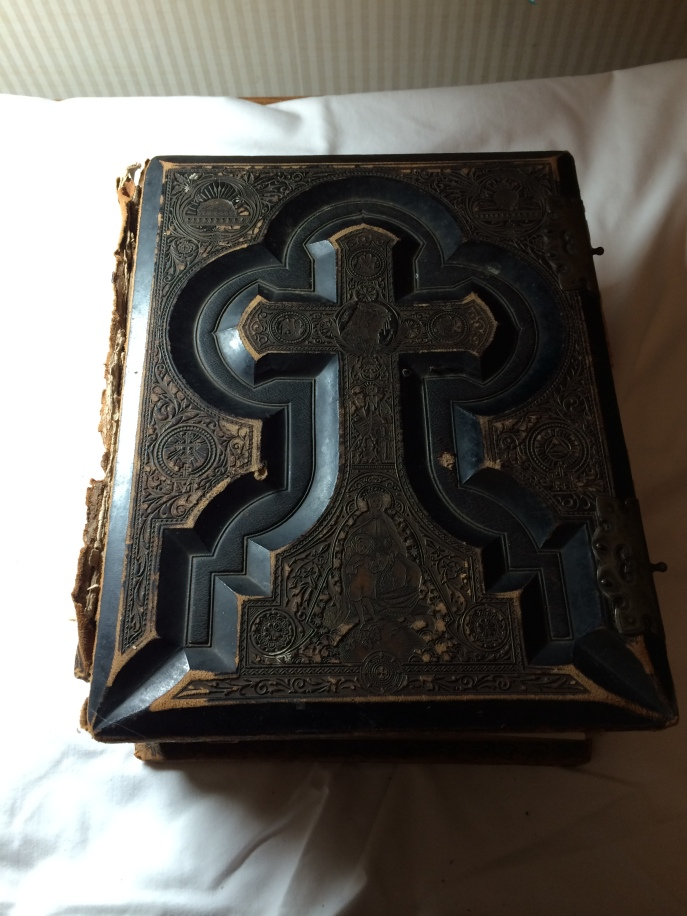 My family's Bible. The cover appears to be carved of wood. There are engravings stamped into it and etched with gold leaf. That same cover is on the top AND bottom of the book.