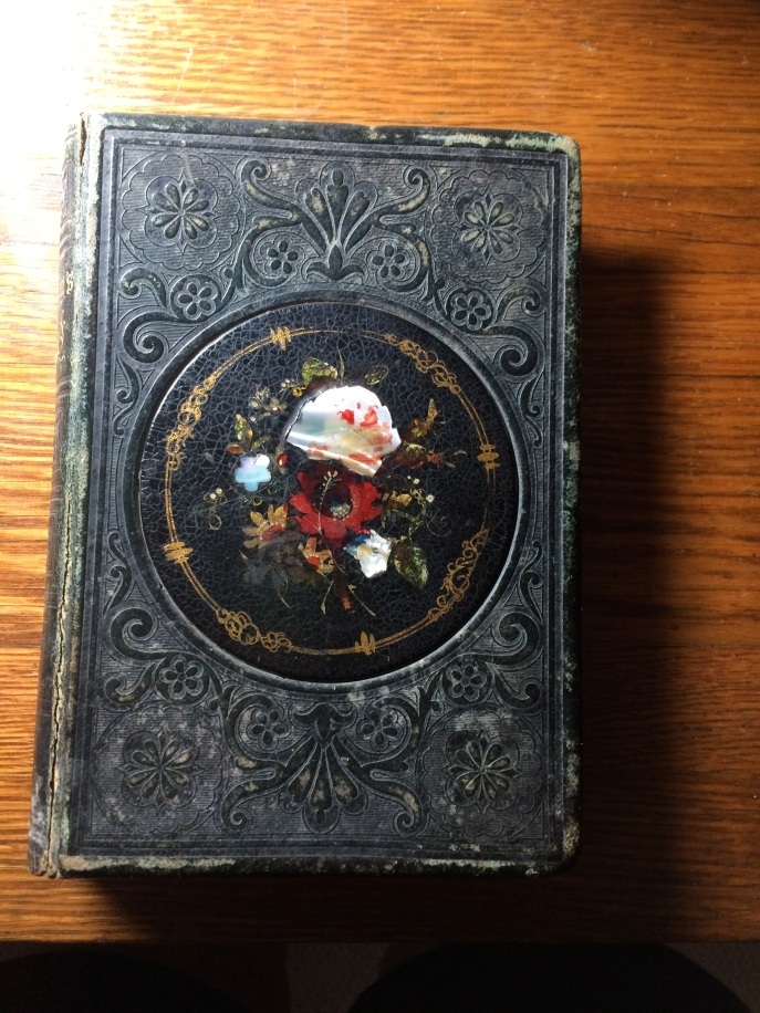 That's a mother-of-pearl on the cover, which is a hard black cover. It isn't leather, and it isn't fabric on the cover.