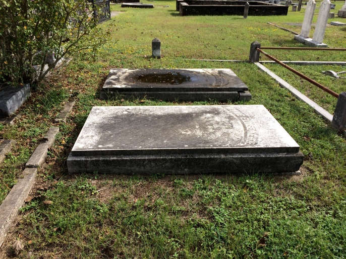 The topmost marker is that of Minnie's parents, Anne and John Kehoe. Minnie's is the bottom marker. The rain has disintegrated much of the engraving on these flat stones.