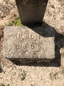 In brass, the years 1861 and 1865. This is right below the footstone with his initials.